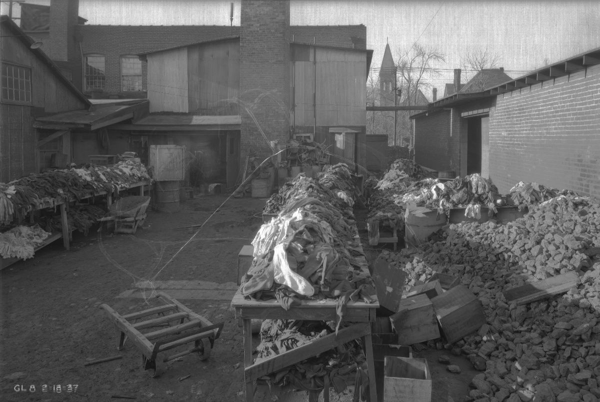 Black and white photograph of an outdoor area of a knitting mill. Long tables contain piles of knitted items such a socks. Rocks and trolleys and wheelbarrows are seen throughout.