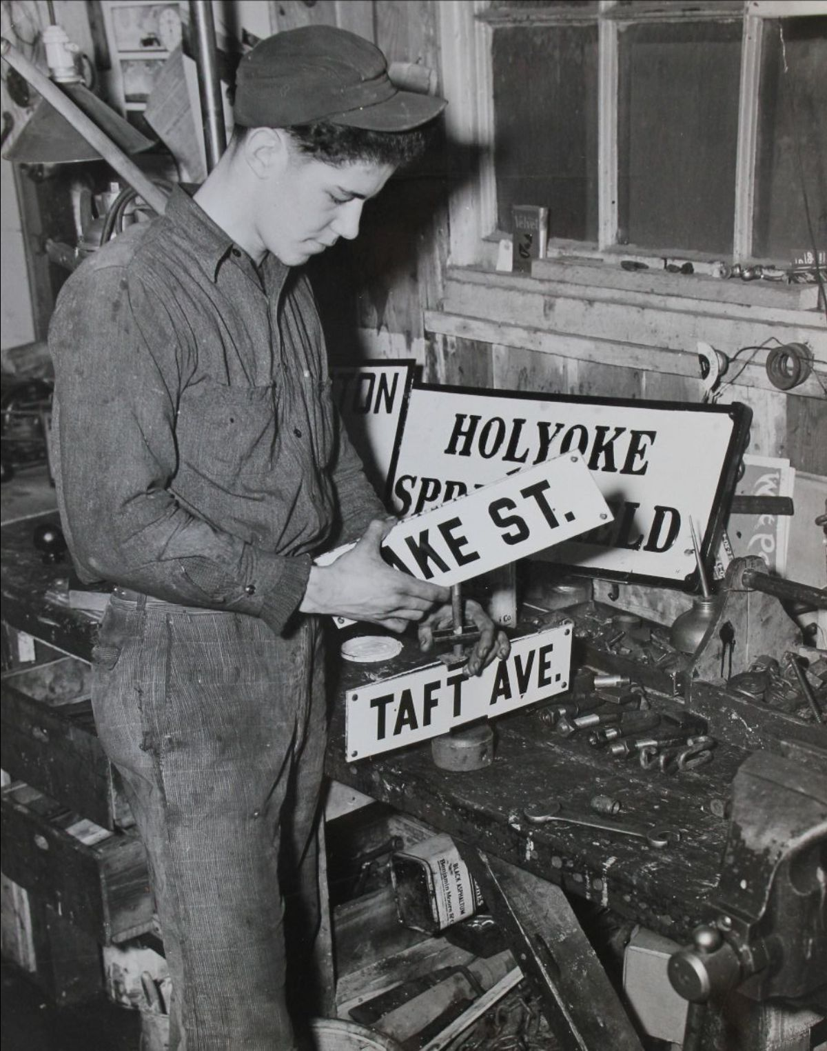 Black and white photograph of a young man assembling street signs