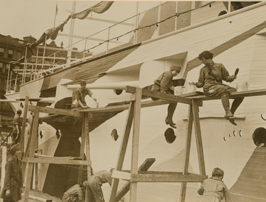 Black and white photograph of group of women painting a battleship with camouflage in New York City