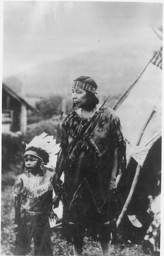 Black and white photo of woman and child by teepee