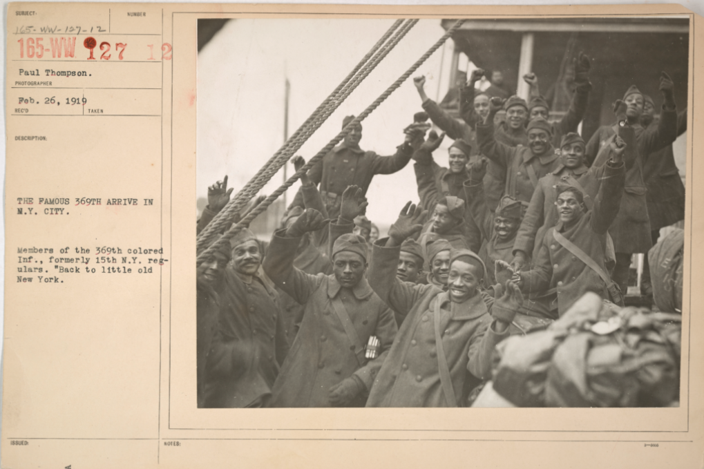 Black and white photograph of a group of African American infantry men arriving in New York City. The men are waving and cheering