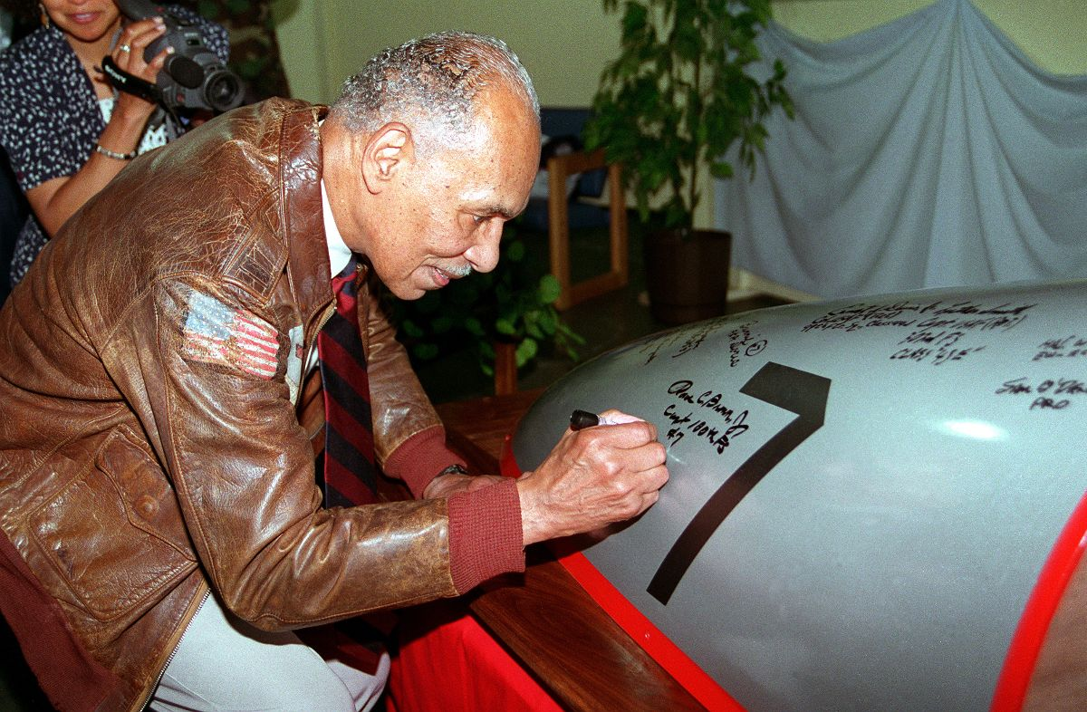 Photograph of Dr. Roscoe Brown, Jr, a Tuskegee Airman, signing the exterior of a plane. Dr. Brown is wearing a brown leather jacket with an American flag on the sleeve. A videographer is filming Dr. Brown in the background.