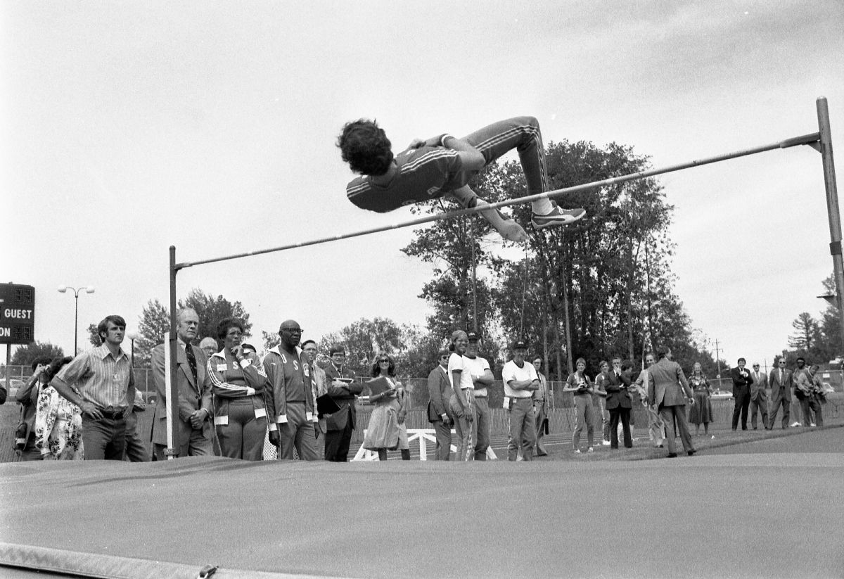 Black and white photograph of a man jumping over the high jump while President Ford observes