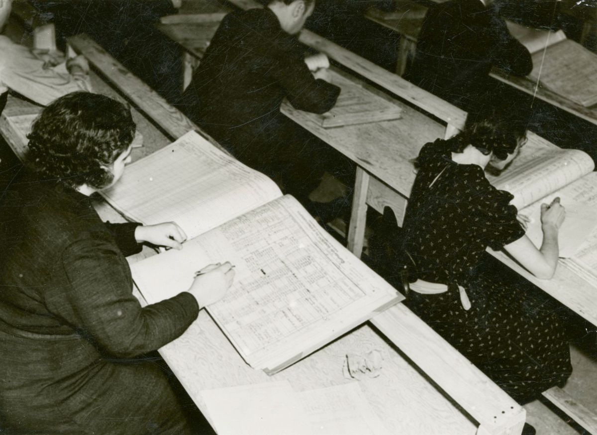 Black and white photograph of workers sitting in rows of desks indexing the 1920 Census records