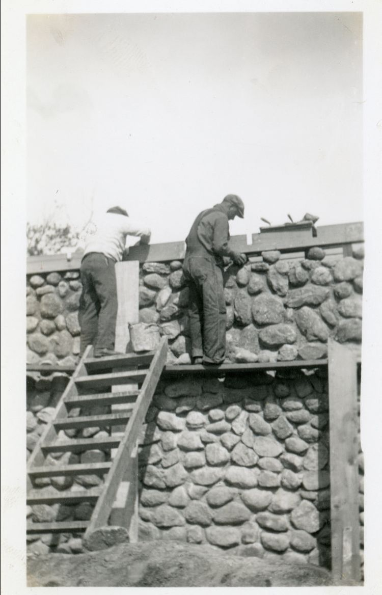 Black and white photo of two men working on stone house construction