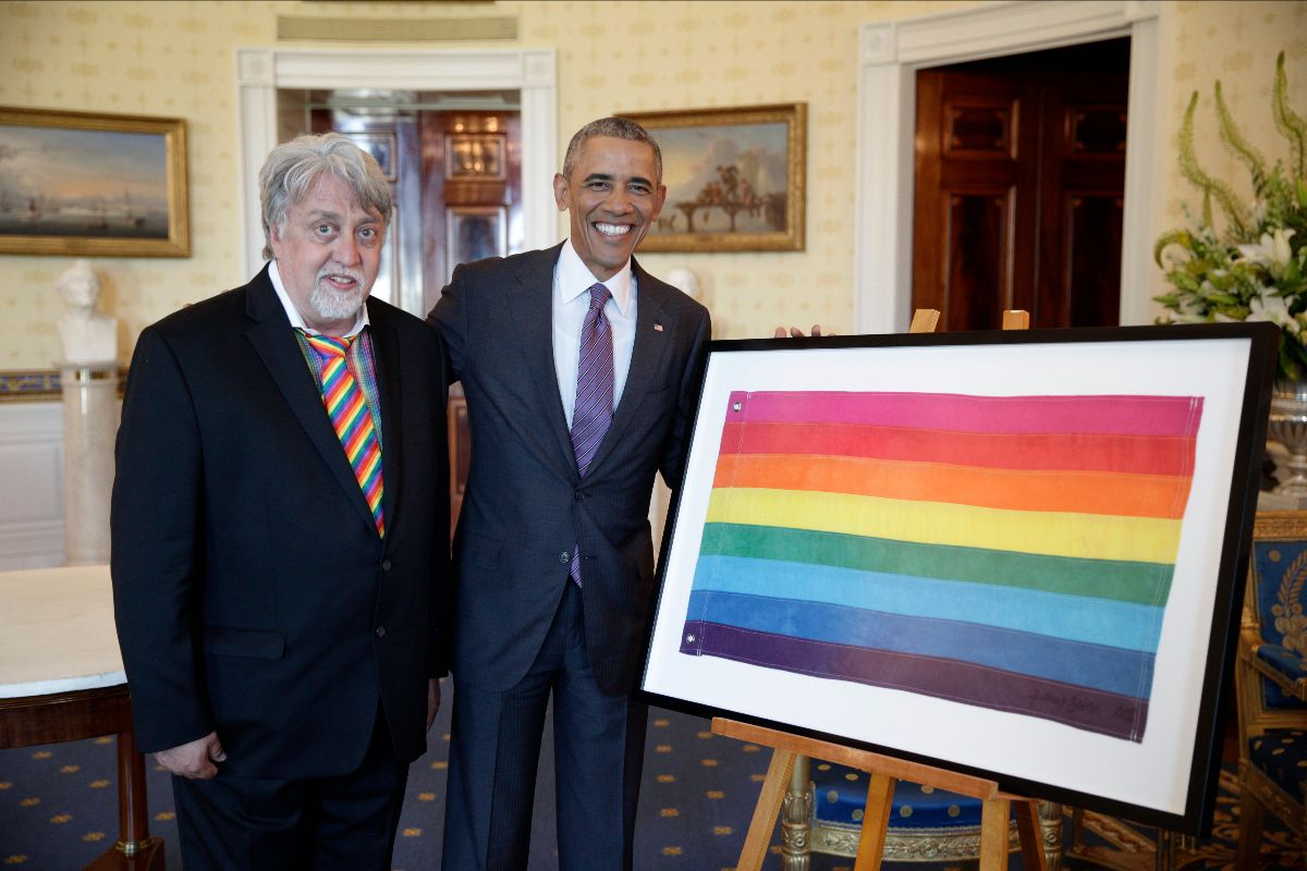 Photograph of President Obama with Gilbert Baker, standing next to a framed Gay Pride Flag in rainbow colors