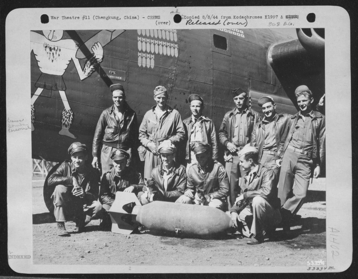 Black and white photograph of the crew of a B-24 standing beside the plane, posing for a photograph