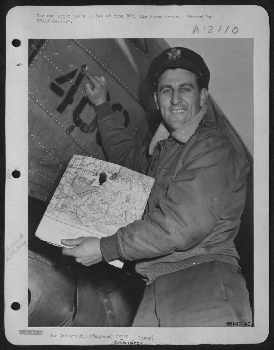 Black and white photograph of a bombadier standing next to his plane and holding a map. He smiles at the camera and points to the hole in his damaged plane.