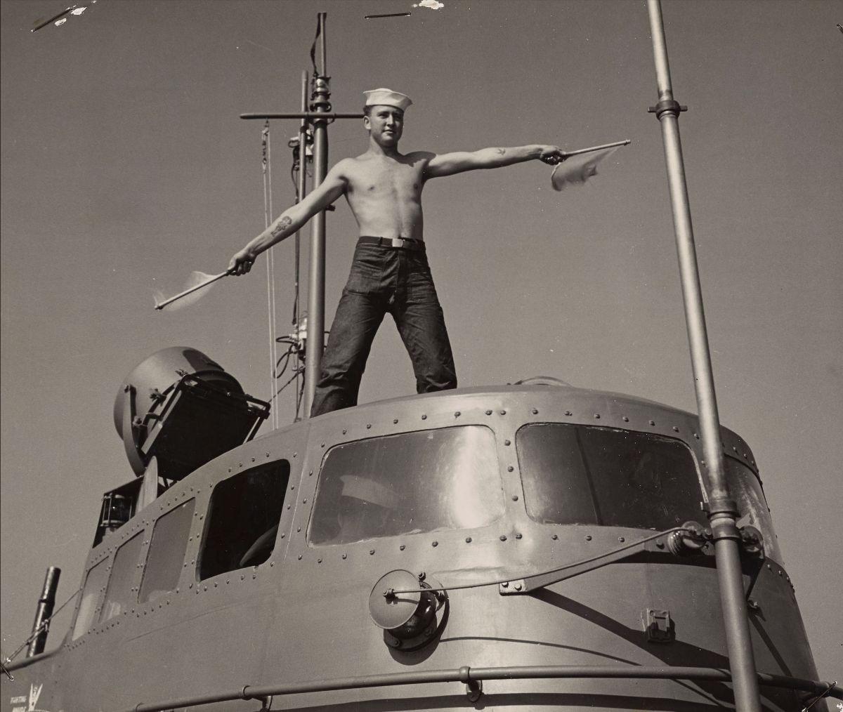 Black and white photograph of a coast guard signalman sending a message with flags while standing on top of a submarine