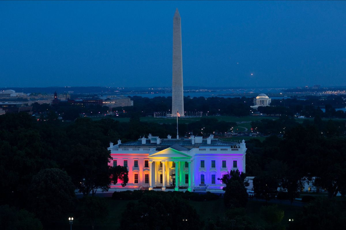 Photograph of the White House at dusk lit in rainbow colors. The Washington Monument can be seen in the background