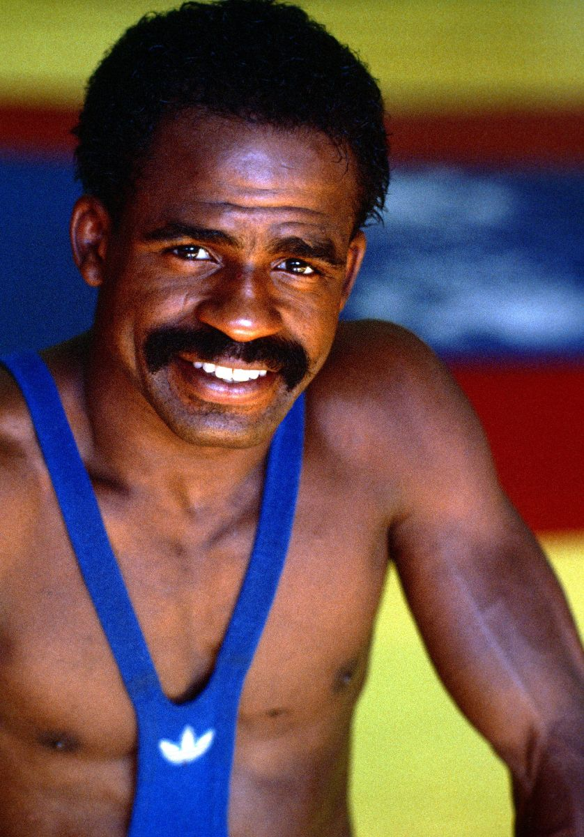 Man in a wrestling uniform smiles at the camera