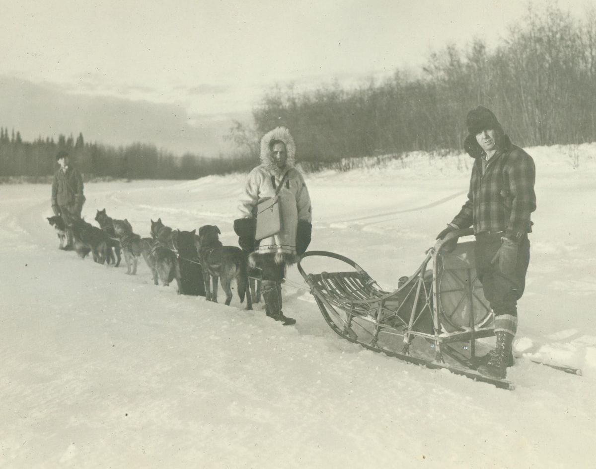 Black and white photograph of three men standing with dogs and a dog sled in the snow