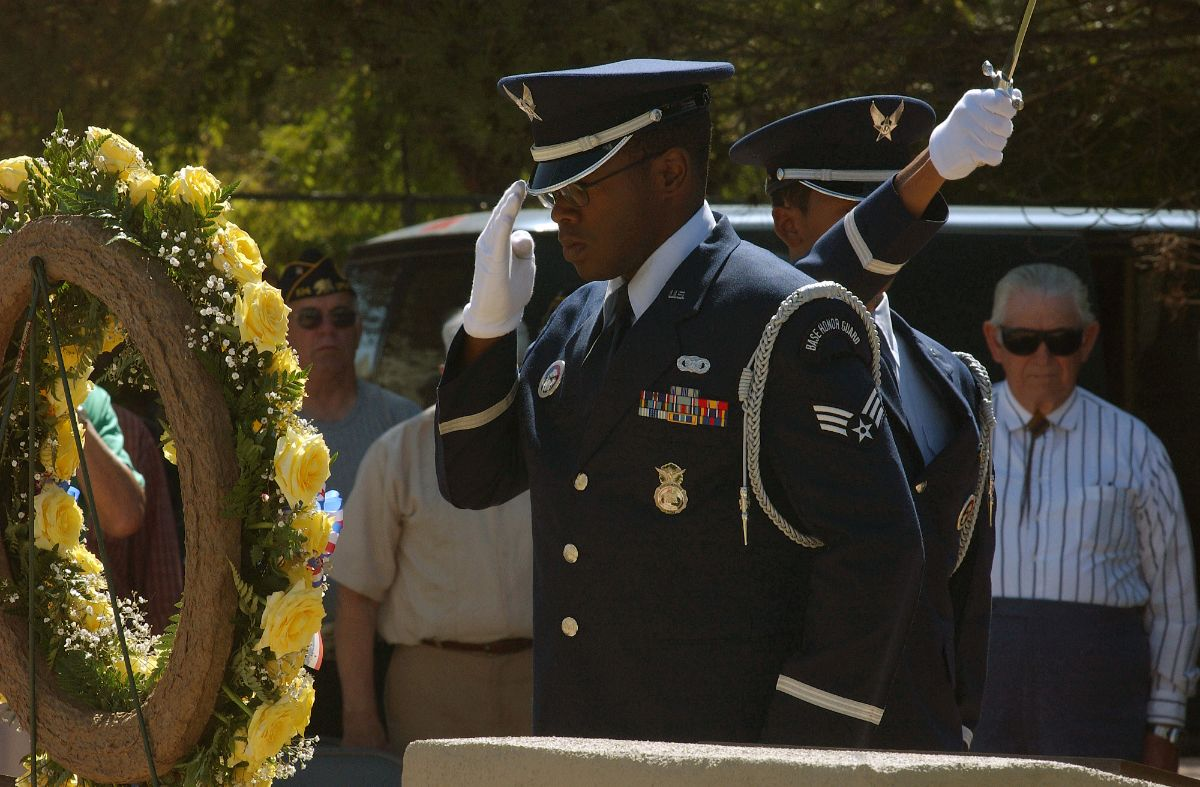 Photograph of Air Force Airman in uniform saluting a wreath. Onlookers stand behind him.
