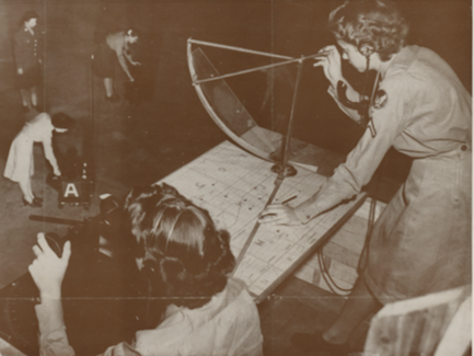 Black and white World War II poster showing women studying detection equipment in an advertisement for the Women's Army Corps