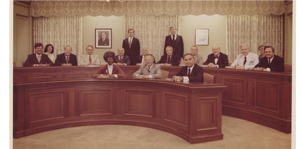 Photograph of rules committee sitting at their seats in Congress. Shirley Chisholm sits in the middle of the front row.