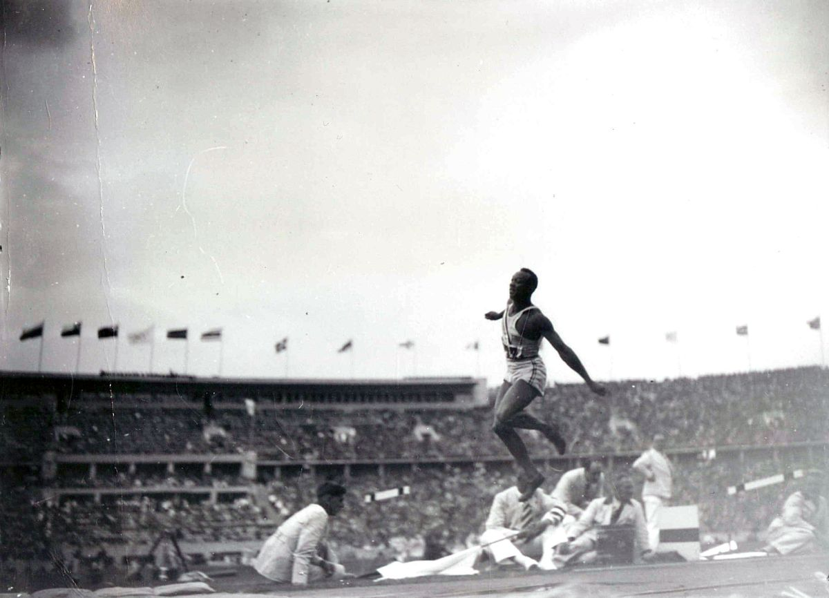 Black and white photograph of Jesse Owens jumping through the air