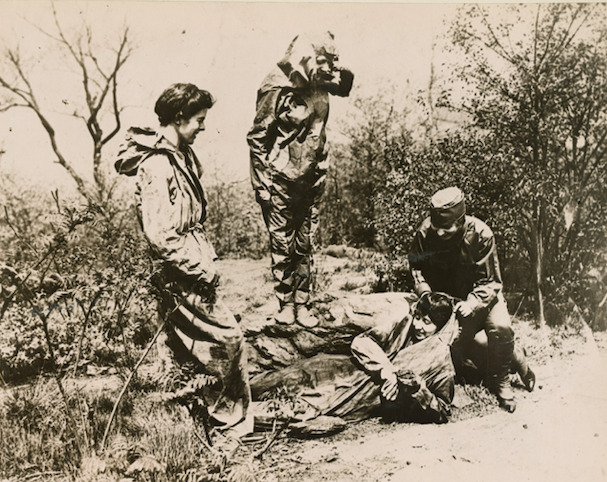 Black and white photograph of group of four women dressed in camouflage suits. One women lies on the ground while another helps her into a suit designed to resemble rock formation