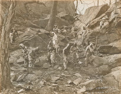 Black and white photograph of group of women dressed in camouflage suits studying the outdoor environment among rocks and trees