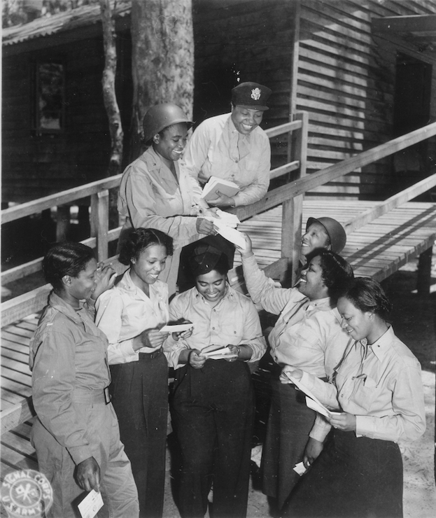 Black and white photograph of a group of women nurses gathering together reading letters.