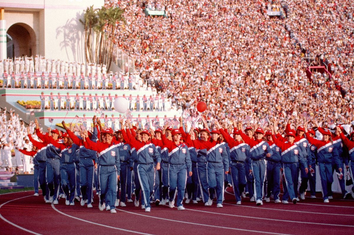 Members of the US olympic team in matching track outfits, walking on the track and waving to the crowd in the stands