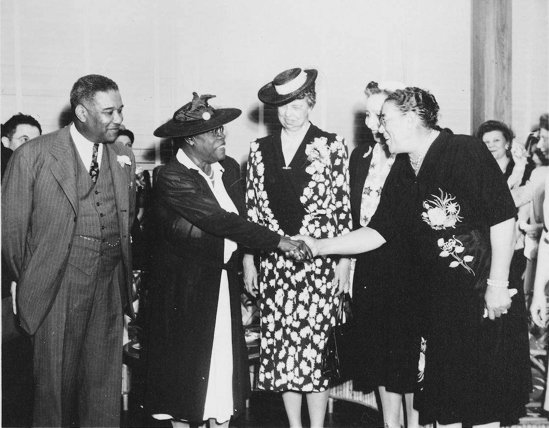 Mary McLeod Bethune shakes hands with a woman while Eleanor Roosevelt looks on