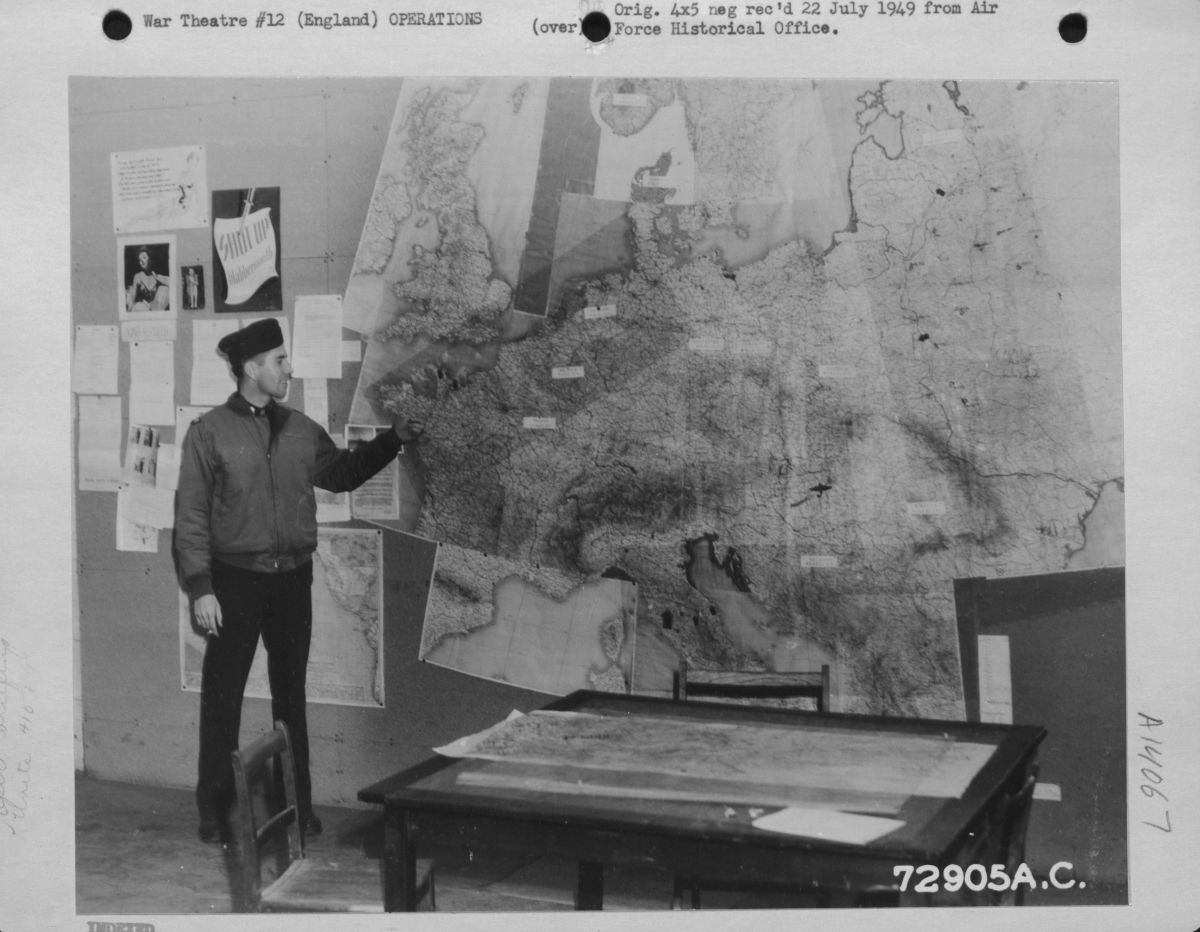 Black and white photograph of an officer pointing to a large map on the wall