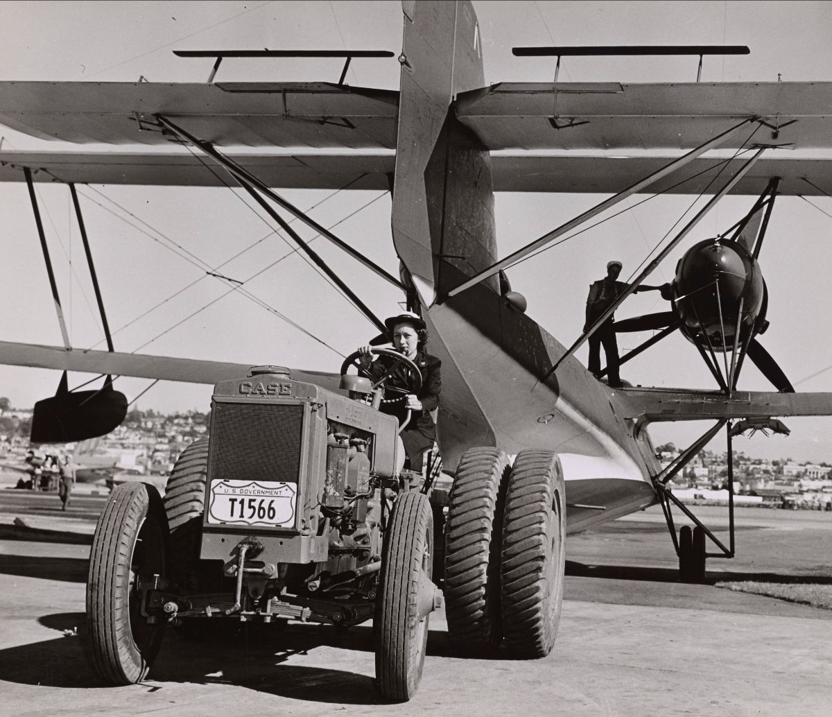 Black and white photograph of a Coast Guard SPAR driving a tractor while towing a seaplane