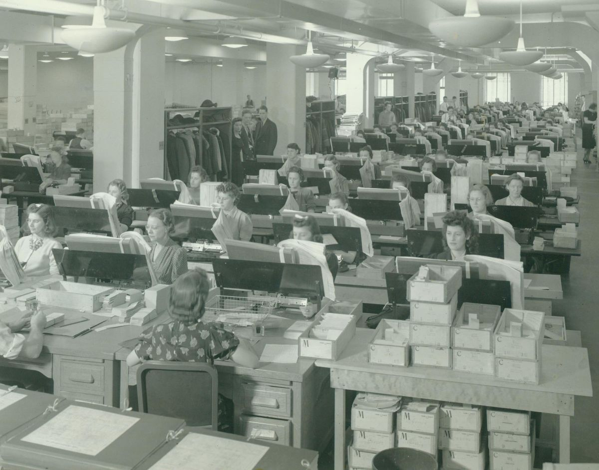 Black and white photograph of card punch operators sitting in rows of desks working. Boxes of cards surround the workers