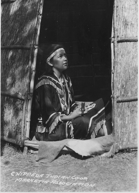 Black and white photograph of a young girl sitting in the doorway of a reed house