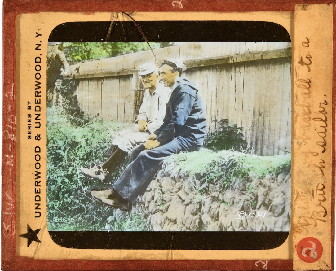 Slide showing two men sitting atop a stone wall talking
