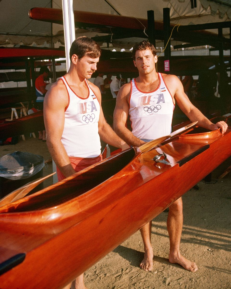 Two olympic athletes hold up their kayak