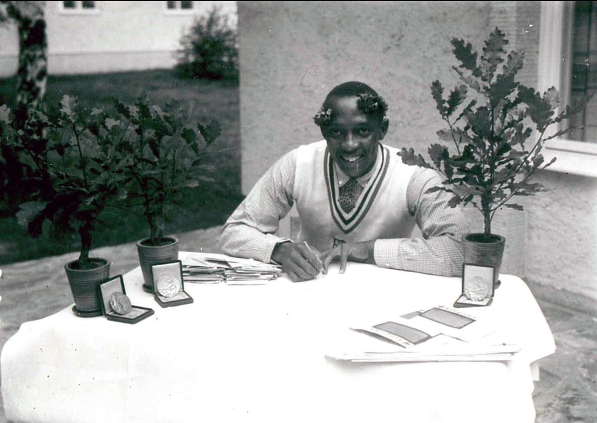 Photograph of Jesse Owens sitting at a table writing with his medals on display