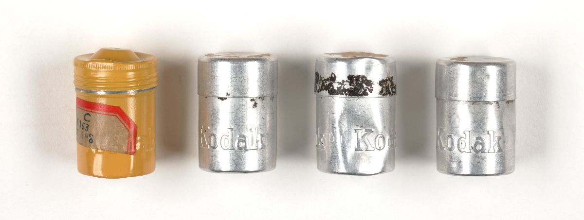 Image of four film canisters from the HUAC investigation of Alger Hiss
