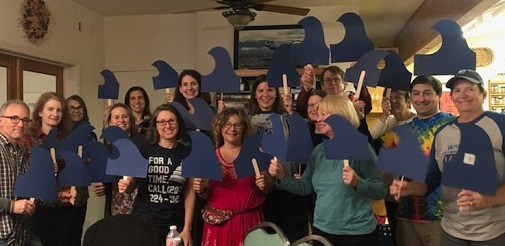 A group of Indivisible Yolo members hold blue wave signs at a general meeting