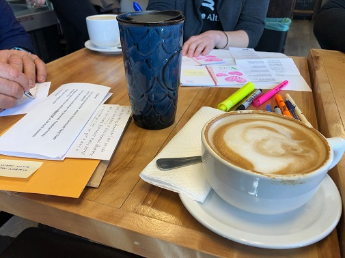 Two people sit at a table with their coffee, writing postcards.