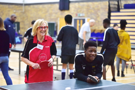 A woman and man stand smiling at a table tennis table holding table tennis bats