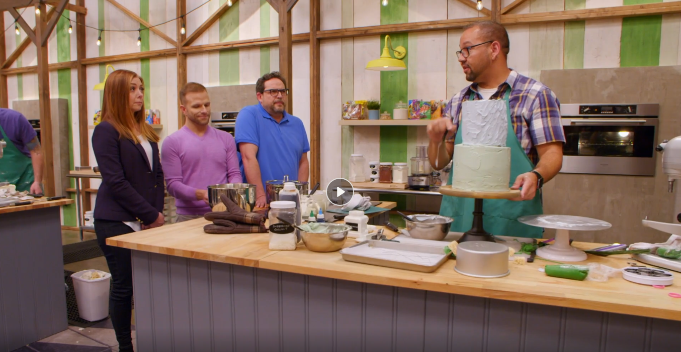 """Employee Jeremy Davis talks with the judges while working on his Mackinac Bridge cake in this screenshot from the Food Network's """"Girl Scout Cookie Championship."""""""
