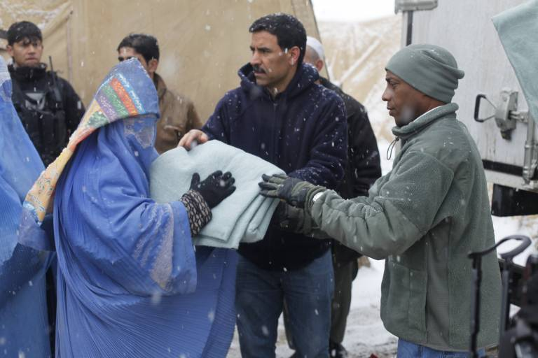 Woman receiving blanket from aid workers