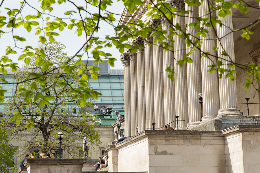 UCL portico behind green leaves