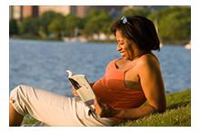 woman reading book by lake