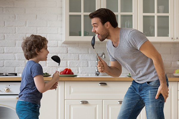 dad and son singing into kitchen spoons