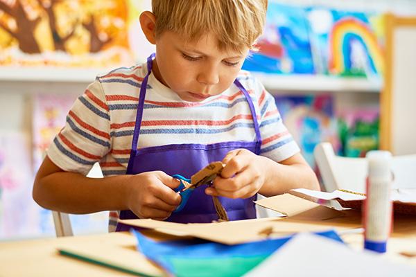 little boy cutting craft paper