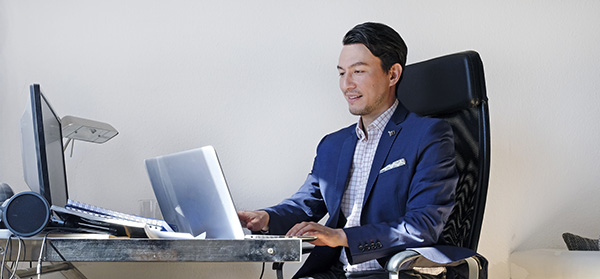 man in suit working on computer while sitting at desk