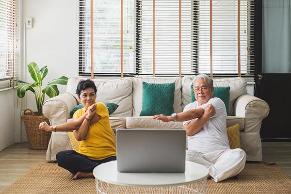 couple doing yoga at home via a laptop