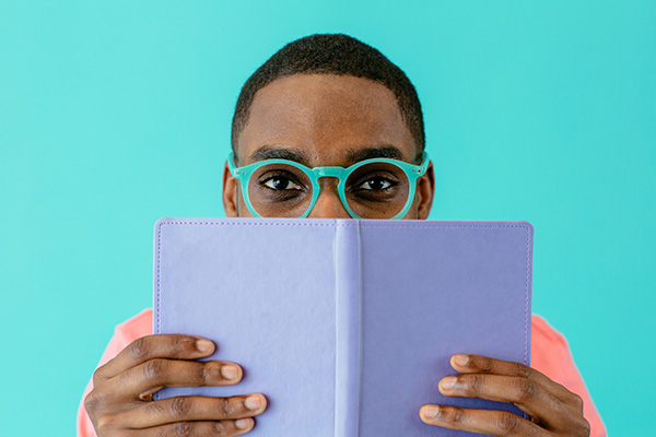 man in glasses peaking above open book