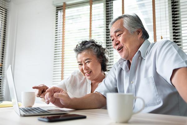 older couple having fun using computer