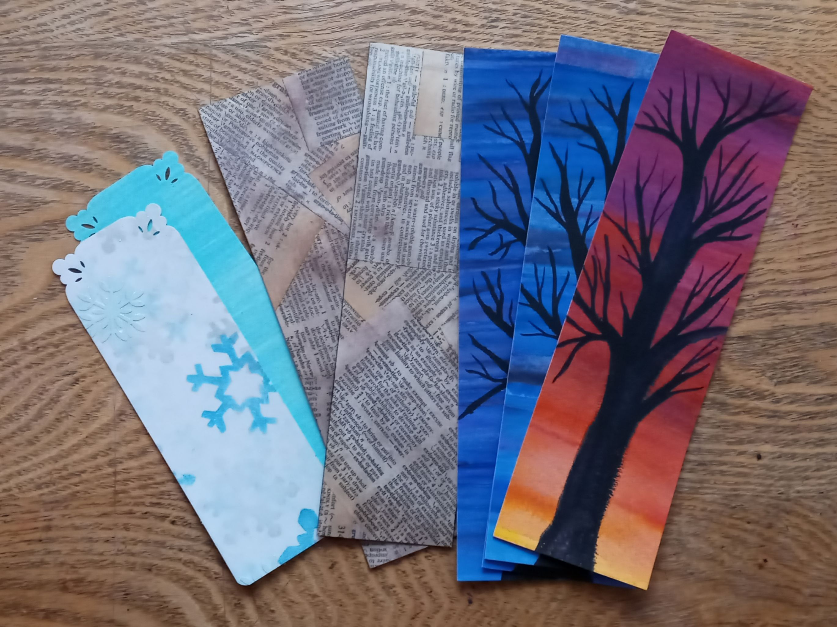 sparkly winter, dictionary and spooky tree bookmarks on plain wood background