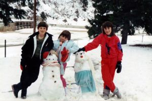 Three children standing around a snowman.