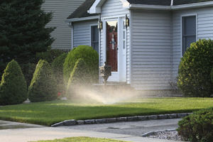 House with sprinkler watering the lawn