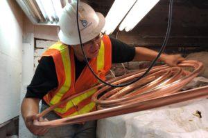 Denver Water Crewmen holding copper pipe.